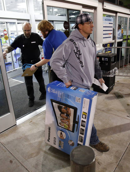 Preston Bryce leaves with his purchase as shoppers enter Best Buy on Interstate 240 for Black Friday Sales on Friday, Nov. 23, 2012, in Oklahoma City, Okla.  Photo by Steve Sisney, The Oklahoman