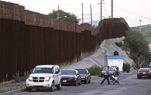 In this Aug. 9, 2012, photo, vehicles are parked along the border fence as pedestrians cross the street in Nogales, Mexico. The location is near the site where a U.S. Border Patrol agent being pelted with rocks opened fire toward Mexico, killing a 16-year-old boy. The shooting has prompted renewed outcry over the Border Patrol�s use-of-force policies and angered human rights activists and Mexican officials who believe the incident has become part of a disturbing trend along the border _ gunning down rock-throwers rather than using non-lethal weapons. (AP Photo/Ross D. Franklin)