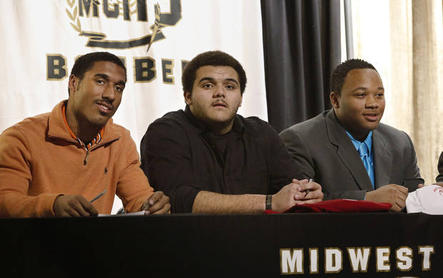 Midwest City High School offensive lineman Carlos Freeman, center, joined fellow players on his football team at a ceremony where they signed letters of intent to play football at various colleges. The signing ceremony was in the school's performing arts building on Wednesday, Feb. 6, 2013.   Photo by Jim Beckel, The Oklahoman
