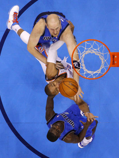 Oklahoma City's Russell Westbrook (0) goes to the basket between Dallas' Chris Kaman (35) and Darren Collison (4) during an NBA basketball game between the Oklahoma City Thunder and the Dallas Mavericks at Chesapeake Energy Arena in Oklahoma City, Thursday, Dec. 27, 2012.  Oklahoma City won 111-105. Photo by Bryan Terry, The Oklahoman