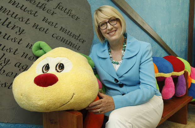 "Robin Khoury, founder of LIttle Light Ministries, sits with a stuffed toy caterpillar named ""Morph"" who will be the mascot for the Little Light Christian School she plans to open in September.  <strong>PAUL HELLSTERN - Oklahoman</strong>"