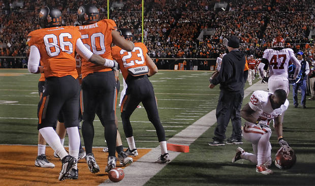 Oklahoma's Roy Finch (22) picks himself off the field as Oklahoma State's Jamie Blatnick (50) celebrates his fumble recovery with teammates during the Bedlam college football game between the Oklahoma State University Cowboys (OSU) and the University of Oklahoma Sooners (OU) at Boone Pickens Stadium in Stillwater, Okla., Saturday, Dec. 3, 2011. Photo by Chris Landsberger, The Oklahoman