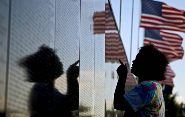 Aubrey McCray, 10, of Norman, looks over the Dignity Memorial Vietnam Wall before an opening ceremony at Reaves Park in Norman, Okla., Wednesday, June 30, 2010.  Photo by Bryan Terry, The Oklahoman
