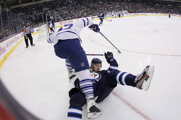 Winnipeg Jets' Bryan Little (18) and Toronto Maple Leafs' Leo Komarov (47) get tangled up in the Jets zone during second period NHL action in Winnipeg on Thursday, Feb. 7, 2013. (AP Photo/The Canadian Press, John Woods)