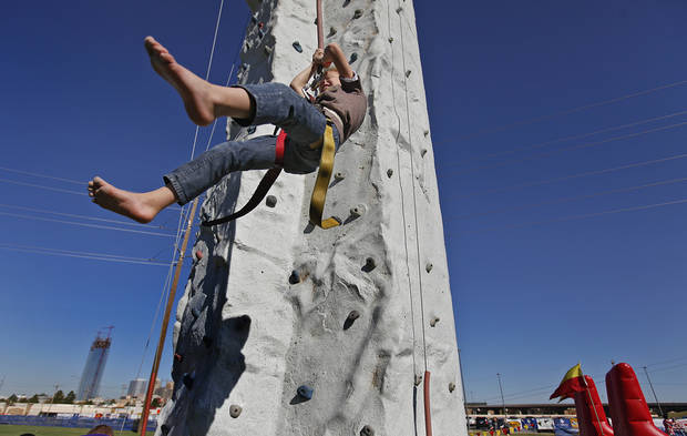 Chris Bachman, 7, swings through the air as he repels off the rockwall in the fan fest area during the Oklahoma Regatta Festival at the Oklahoma River on Saturday, Oct. 1, 2011, in Oklahoma City, Okla. Photo by Chris Landsberger, The Oklahoman