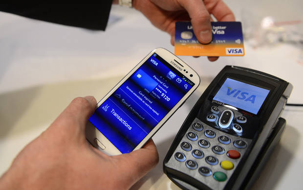 FILE - In this Feb. 27, 2013 photo, a man uses the NFC payment Visa system at the Mobile World Congress, the world's largest mobile phone trade show, in Barcelona, Spain. (AP Photo/Manu Fernandez, File)