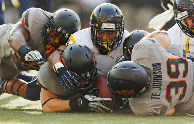 Oklahoma State's Nico Ornelas (41), middle, recovers a fumbled West Virginia kickoff return between teammates Kris Catlin (32), left, and Teddy Johnson (39), right, while underneath West Virginia's Andrew Buie (13) in the second quarter during a college football game between Oklahoma State University (OSU) and West Virginia University (WVU) at Boone Pickens Stadium in Stillwater, Okla., Saturday, Nov. 10, 2012. Photo by Nate Billings, The Oklahoman