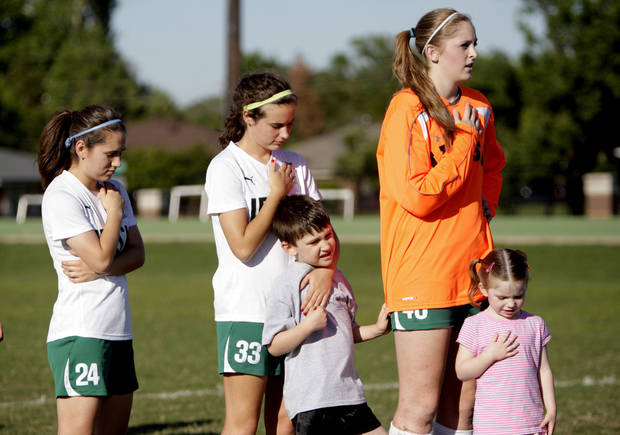Rochelle Garcia, Nicole Voss  and Elyse Hight, Bishop McGuinness High School girls soccer team members, sing the National Anthem with Rob Medley, 6, and Ruthie Medley, 4, at a soccer game on Tuesday at Bishop MicGuinness. Rob Medley is a student at Good Shepherd Catholic School at Mercy. <strong>SARAH PHIPPS - SARAH PHIPPS</strong>