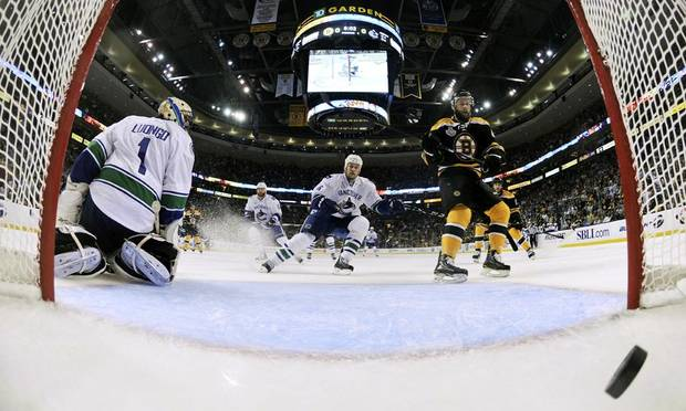 Boston Bruins center Rich Peverley (49) watches as the puck slides to the back of the net as Vancouver Canucks goalie Roberto Luongo (1) looks on in the first period during Game 4 of the NHL hockey Stanley Cup finals, Wednesday, June 8, 2011, in Boston. (AP Photo/Harry Howe, Pool) ORG XMIT: BXG125