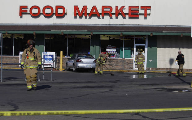 Firefighters clean up the scene outside a grocery store where two police officers were fatally shot as they investigated a suspicious vehicle, in Topeka, Kan., Monday, Dec. 17, 2012. A suspect in the killings is dead after a nearly two-hour armed standoff, authorities said Monday. (AP Photo/Orlin Wagner)