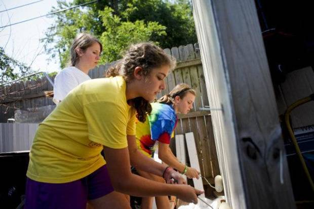 From left, Dana Murray, Annie Armstrong and Allese Lewis paint a shed for Dale Osborne as they volutneer with the Catholic HEART Workcamp. Volunteers are helping Osborne and his neighbors this week in the Riverpark neighborhood in southwest Oklahoma City. <strong>ZACH GRAY - THE OKLAHOMAN</strong>