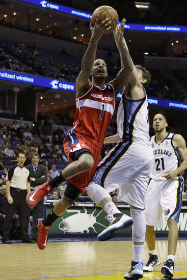 Washington Wizards  forward Trevor Ariza (1) goes to the basket over Memphis Grizzlies' Marc Gasol, of Spain, as Grizzlies' Tayshaun Prince (21) watches during the first half of an NBA basketball game in Memphis, Tenn., Friday, Feb. 1, 2013. (AP Photo/Danny Johnston)