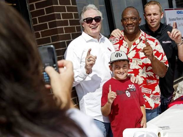 Christina Holland takes a picture of her son, Carter Holland, 11, with University of Oklahoma Heisman Trophy winners Steve Owens, left, Billy Sims and Jason White on Friday during Bevo Bash in Marietta on the day before the OU-Texas football game. Photo by Bryan Terry, The Oklahoman