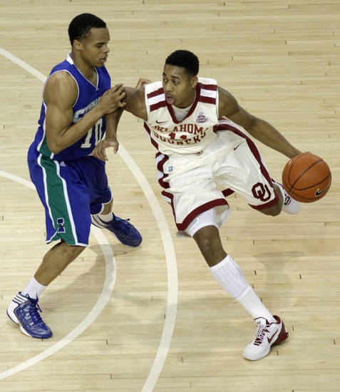 OU: Oklahoma's Isaiah Cousins (11) drives the ball past Texas A&M's Johnathan Jordan (10) during a college basketball game between the University of Oklahoma and Texas A&M Corpus Christi at McCasland Field House in Norman, Okla., Monday, Dec. 31, 2012.  Photo by Garett Fisbeck, For The Oklahoman