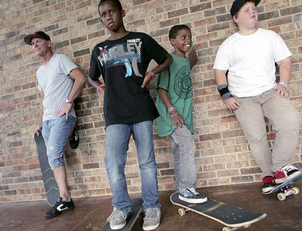 Steve McNutt (left) watches a younger generation of skaters, Aaron Ward, Moses Ward and Nathan Zaloudek, all of Edmond, during a skate demonstration outside the Edmond Public Library in Edmond on Monday, July 12, 2010. Photo by John Clanton, The Oklahoman ORG XMIT: KOD