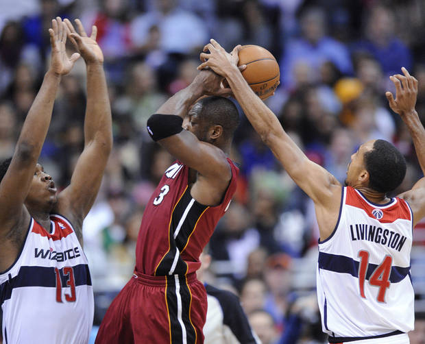 Washington Wizards' Kevin Seraphin (13), of France, and Shaun Livingston (14) defend Miami Heat guard Dwyane Wade (3) during the second half of an NBA basketball game, Tuesday, Dec. 4, 2012, in Washington. The Wizards won 105-101. (AP Photo/Nick Wass)