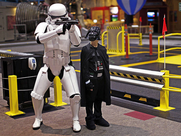 Landon Hood, 9, of Dale, looks up at Mark Elden as they get their photo taken during the Science Museum Oklahoma�s Bright Night of Star Wars sleepover.