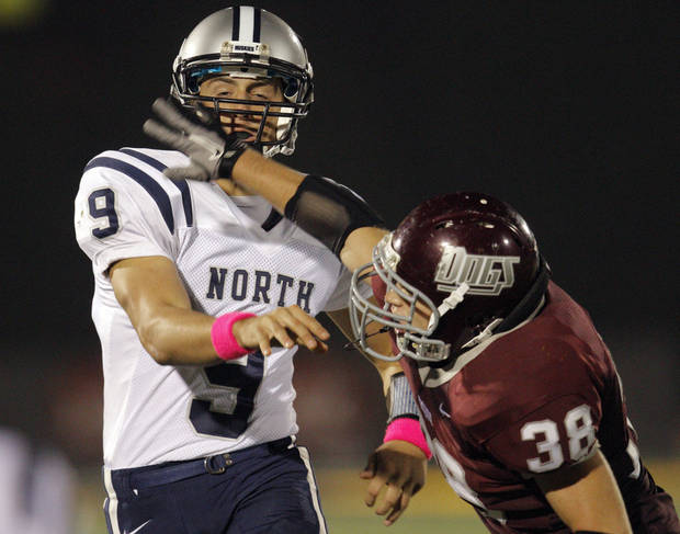 Edmond Memorial's Chase Thackerson pressures Edmond North's Luke Hoskins during the high school football game between Edmond North and Edmond Memorial at Wantland Stadium in Edmond, Okla., Friday, Sept. 16, 2011. Photo by Sarah Phipps, The Oklahoman