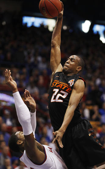 Oklahoma State guard Markel Brown (22) dunks while covered by Kansas forward Thomas Robinson (0) during the second half of an NCAA college basketball game in Lawrence, Kan., Saturday, Feb. 11, 2012. Brown scored 21 points in the game. Kansas defeated Oklahoma State 81-66. (AP Photo/Orlin Wagner) <strong>Orlin Wagner</strong>