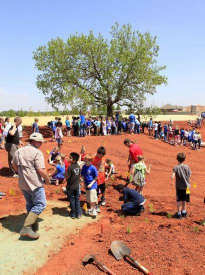 Students and volunteers from Tinker Air Force Base and other community agencies plant native aquatic plants in the wetlands outdoor classroom under construction at Deer Creek Grove Valley Elementary School. PHOTO BY PAUL B. SOUTHERLAND, THE OKLAHOMAN <strong>PAUL B. SOUTHERLAND</strong>
