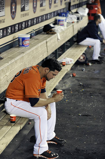 Houston Astros relief pitcher Xavier Cedeno sits alone in the dugout after failing to record an out in a seven-run fifth inning against the Oakland Athletics in a baseball game Friday, April 5, 2013, in Houston. (AP Photo/Pat Sullivan)