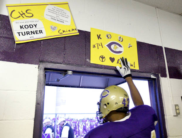 TJ Filer touches a poster honoring Kody Turner before running onto the field at the football game between Chickasha and Capitol Hill at Chickasha High School, Friday, Oct. 1, 2010. It was the first home game since the death of player Kody Turner. Photo by Sarah Phipps, The Oklahoman