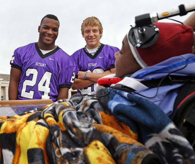 Bethany football players Dorien Jackson, left, and Jimmy Lovelace talk to Brandon, a patient at The Children's Center, during an event at the center in Bethany, Okla., Thursday, Sept. 27, 2012. The Bethany football team visited the center as part of the lead up to The Children's Center Bowl. Photo by Nate Billings, The Oklahoman