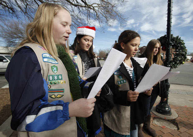 Girl Scouts, from left, Rachel Barrett, Eleni Tsaras, Brooklyn Phillips and Emma Harper sing Christmas carols in downtown Edmond.  PHOTO BY PAUL HELLSTERN, THE OKLAHOMAN