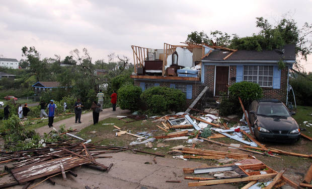 "Homeowners survey damage after a tornado hits Pratt City just north of downtown Birmingham on Wednesday, April 27, 2011, in Birmingham, Ala.   The widespread destruction caused Gov. Robert Bentley to declare a state of emergency by midday, saying tornadoes, severe thunderstorms, hail, and straight-line winds caused damage to ""numerous homes and businesses"" in Alabama. (AP Photo/Butch Dill)"