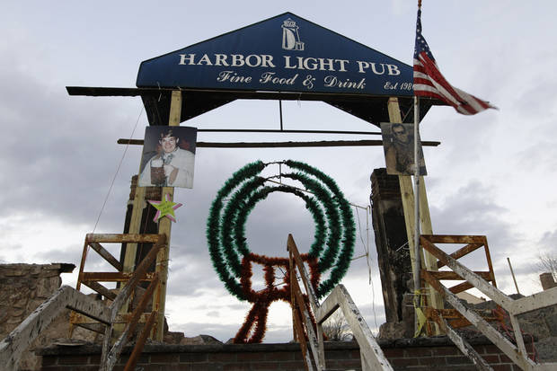 A Christmas wreath adorns the entrance to the burned-out Harbor Light Pub, a neighborhood hangout and gathering place for Rockaways residents, before it burned during Superstorm Sandy, in the Belle Harbor section of the Queens borough of New York, Wednesday, Dec. 5, 2012.  The Irish pub was a favorite of local firefighters and police officers.  Portraits of two neighborhood boys frame the entrance to the pub.  At left is Charlie Heeran, son of pub owner Bernie Heeran. The younger Heeran died in the 9-11 World Trade center attacks.  At right is Michael Glover, a Marine who enlisted because of 9-11, but was killed in Fallujah, Iraq, in 2006. (AP Photo/Kathy Willens)