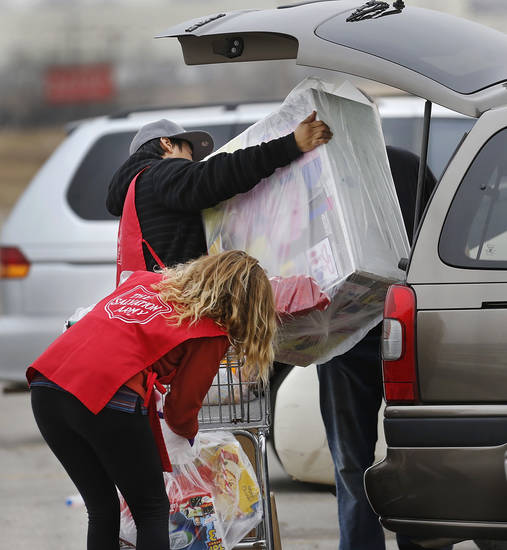 T. J. Suetopka lifts a large box into the back of a client's car as Katy Weaver pulls other bags of gifts and toys from the shopping cart.  Weaver and Suetopka are part of about two dozen volunteers from Oklahoma County Commissioner Brian Maughan's SHINE project, a  volunteer community service campaign.  The Salvation Army and Feed the Children teamed to distribute bicycles and toys for children,  and handed out boxes of food for families at their annual distribution event Wednesday, Dec. 19, 2012. Salvation Army officials said 100 volunteers helped make the event go smoothly. The volunteers loaded bags of toys and bikes into vehicles of clients who had been pre-approved for assistance.  Many of the gifts were provided through the Salvation Army's Angel Tree program   Photo by Jim Beckel, The Oklahoman
