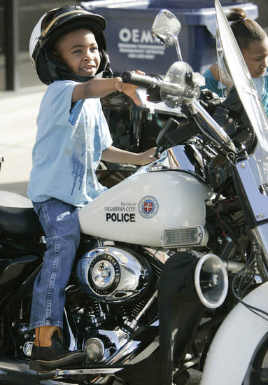 Robert Taylor Jr., 6, sits on an Oklahoma City police motorcycle Monday before the start of the Martin Luther King Jr. Day parade in Oklahoma City.