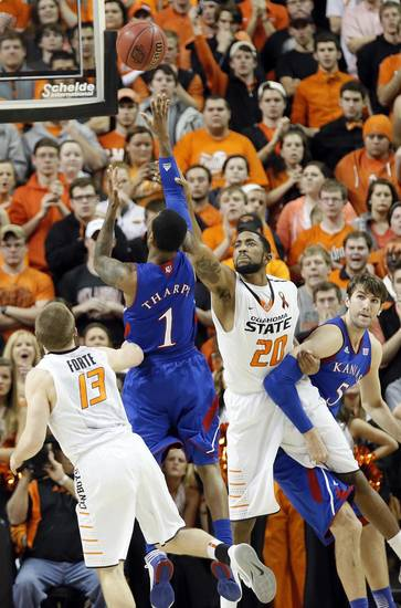 Kansas' Naadir Tharpe (1) puts up a shot over Oklahoma State 's Michael Cobbins (20) during the college basketball game between the Oklahoma State University Cowboys (OSU) and the University of Kanas Jayhawks (KU) at Gallagher-Iba Arena on Wednesday, Feb. 20, 2013, in Stillwater, Okla. Photo by Chris Landsberger, The Oklahoman