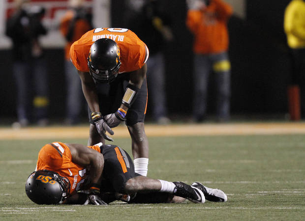 Oklahoma State's Justin Blackmon (81) checks on an injured Oklahoma State's Jeremy Smith (31) during the Bedlam college football game between the Oklahoma State University Cowboys (OSU) and the University of Oklahoma Sooners (OU) at Boone Pickens Stadium in Stillwater, Okla., Saturday, Dec. 3, 2011. Photo by Chris Landsberger, The Oklahoman