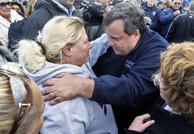 "FILE - In this Nov. 2, 2012 file photo, New Jersey Gov. Chris Christie, right, meets Bonnie Miller after touring devastation from Superstorm Sandy in Brick, N.J. Christie can't get enough of ""Saturday Night Live."" One day after ducking questions about Twinkies-maker Hostess shutting down to avoid giving comedians fodder and saying he's on ""SNL"" enough, Christie made a cameo appearance, Saturday, Nov. 17, 2012, on ""Weekend Update."" The tough-talking governor poked fun at his notoriously short temper and the familiar blue fleece jacket that he has worn while touring the state following Superstorm Sandy. (AP Photo/Mel Evans, File)"