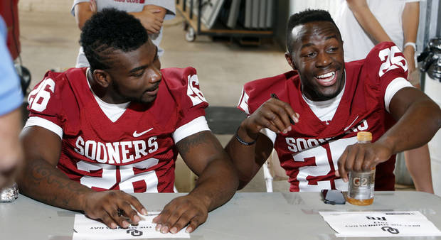 Running backs Damien Williams and  David Smith sign autographs during fan appreciation day for the University of Oklahoma Sooner (OU) football team at Gaylord Family-Oklahoma Memorial Stadium in Norman, Okla., on Saturday, Aug. 3, 2013. Photo by Steve Sisney, The Oklahoman