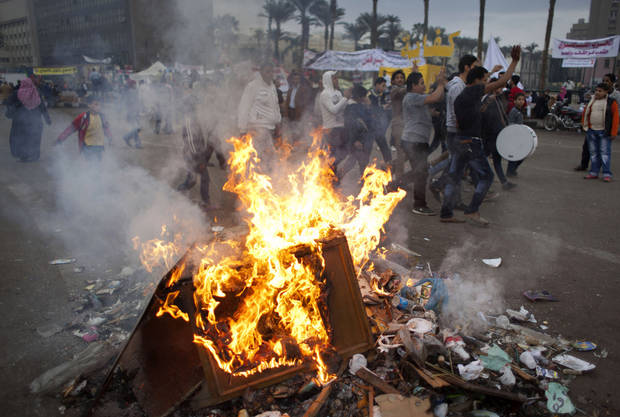 Protesters opposed to Egyptian President Mohammed Morsi chant slogans near burning garbage at Tahrir Square in Cairo, Egypt, Wednesday, Dec. 5, 2012. Supporters and opponents of Egyptian leader Mohammed Morsi fought with rocks, firebombs and sticks outside the presidential palace in Cairo on Wednesday, as a new round of protests deepened the country�s political crisis. (AP Photo/Nasser Nasser)