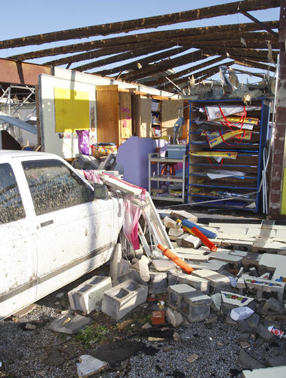 A car parked outside a school is covered in rubble after a wall fell on it in Tushka, Okla., Friday, April 15, 2011 after a tornado the night before. (AP Photo/Sue Ogrocki)