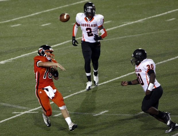 Booker T. Washington quarterback Bennett White (16) passes while being chased by Douglass defenders during the Douglass-Booker T. Washington season opener, on Friday, Aug. 31, 2012. CORY YOUNG/Tulsa World