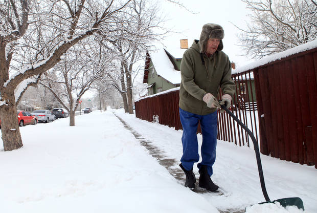 Dean Johnson clears snow from his sidewalk on Eleventh Street in Rapid City, S.D., Wednesday, April 17, 2013 after another April storm brought more snow to the area. (AP Photo/Rapid City Journal, Chris Huber)