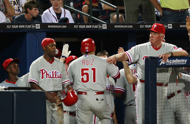 Philadelphia Phillies' Carlos Ruiz (51) is greeted at the dugout by manager Charlie Manuel, right, and Jimmy Rollins after hitting a three-run home run in the seventh inning of a baseball game against the Atlanta Braves in Atlanta, Wednesday, May 2, 2012. (AP Photo/John Bazemore)
