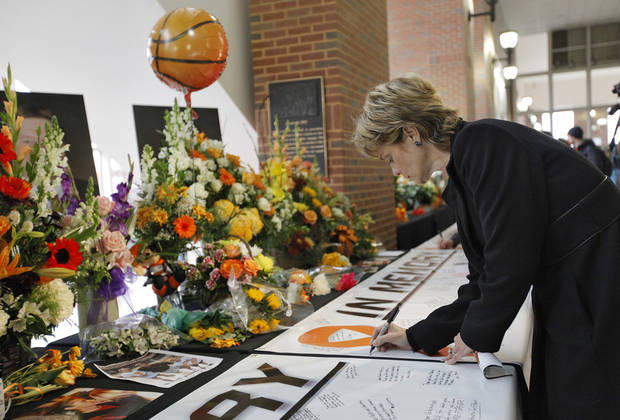 Baylor University women's basketball coach Kim Mulkey signs the memory banner during the memorial service for Oklahoma State head basketball coach Kurt Budke and assistant coach Miranda Serna at Gallagher-Iba Arena on Monday, Nov. 21, 2011 in Stillwater, Okla. The two were killed in a plane crash along with former state senator Olin Branstetter and his wife Paula while on a recruiting trip in central Arkansas last Thursday. Photo by Chris Landsberger, The Oklahoman