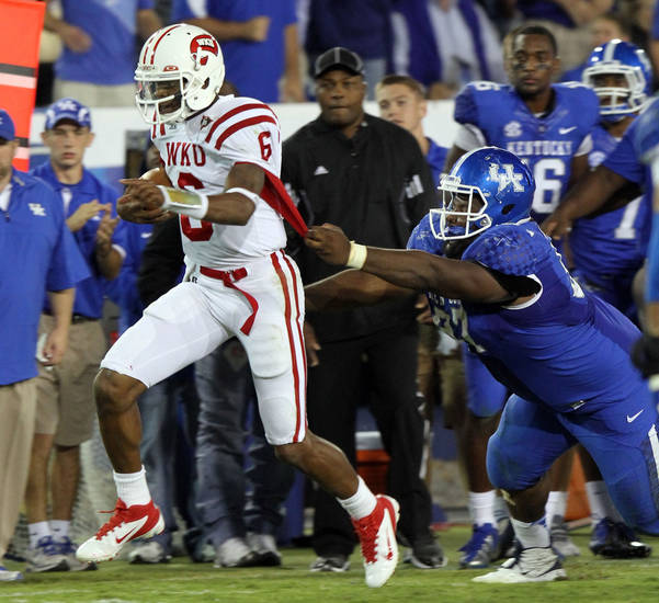 Western Kentucky's Kawaun Jakes, left, escapes the grasp of Kentucky's Mister Cobble during an overtime NCAA college football game at Commonwealth Stadium in Lexington, Ky., Saturday, Sept. 15, 2012. Western Kentucky won 32-31. (AP Photo/James Crisp)