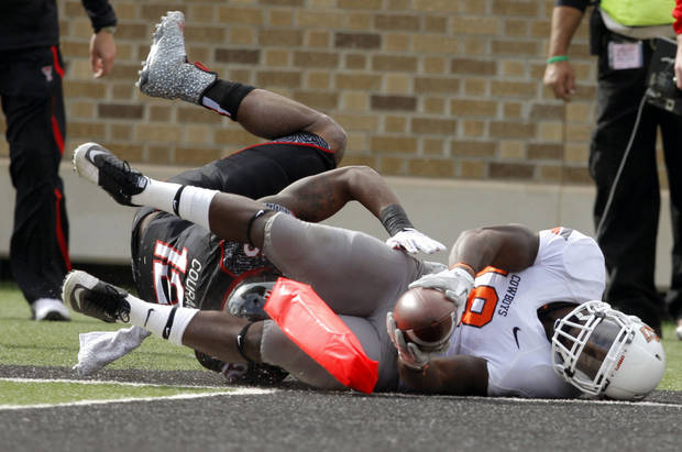 Oklahoma State's Herschel Sims (18) dives for the end zone as Texas Tech's D.J. Johnson (12) tackles him during a college football game between Texas Tech University (TTU) and Oklahoma State University (OSU) at Jones AT&T Stadium in Lubbock, Texas, Saturday, Nov. 12, 2011.  Photo by Sarah Phipps, The Oklahoman  ORG XMIT: KOD
