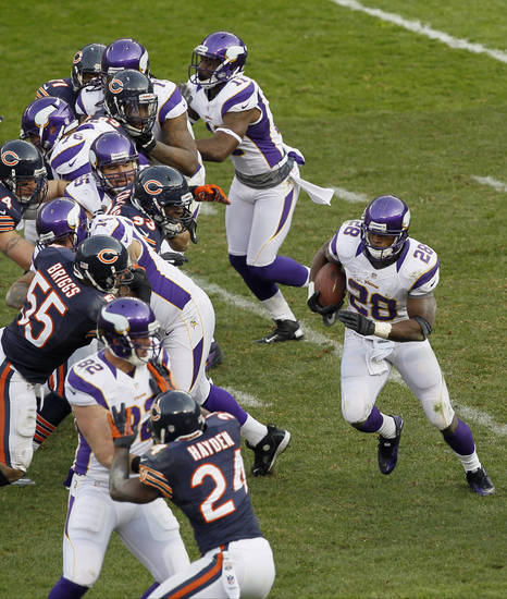 Minnesota Vikings running back Adrian Peterson (28) looks for an opening against the Chicago Bears in the second half of an NFL football game in Chicago, Sunday, Nov. 25, 2012. (AP Photo/Charles Rex Arbogast)