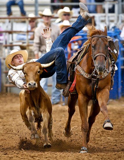 Kade Kressman, of Bascom, Fla., leaps for his steer as he competes in the steer wrestling event during the International Finals Youth Rodeo at the Heart of Oklahoma Expo Center in Shawnee on Thursday, July 15, 2010.    Photo by Chris Landsberger, The Oklahoman