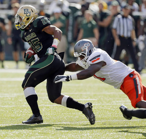 Baylor's Lache Seastrunk (25) breaks away from Oklahoma State's Shaun Lewis (11) during a college football game between the Oklahoma State University Cowboys (OSU) and the Baylor University Bears at Floyd Casey Stadium in Waco, Texas, Saturday, Dec. 1, 2012. Photo by Nate Billings, The Oklahoman