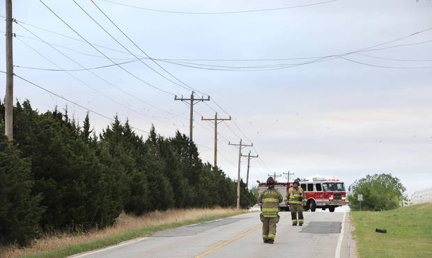 Oklahoma City firemen looking at power lines dislodged by high winds on Hefner Road just east of Kelley Ave. in Oklahoma City Friday, April 15, 2011. Firemen closed Hefner and stayed on the scene in case sparks from the lines created a grass fire. Photo by Paul B. Southerland, The Oklahoman