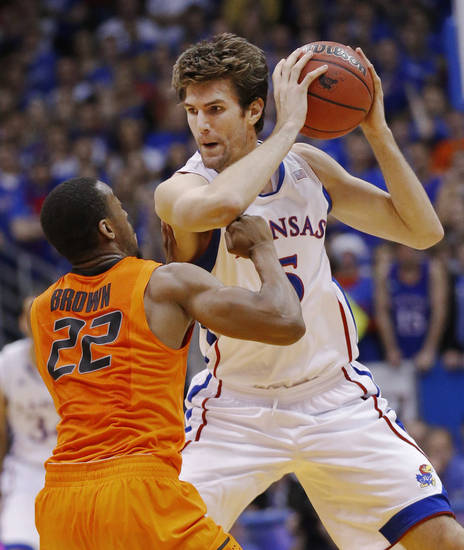 Kansas center Jeff Withey (5) holds the ball away from Oklahoma State guard Markel Brown (22) during the first half of an NCAA college basketball game in Lawrence, Kan., Saturday, Feb. 2, 2013. (AP Photo/Orlin Wagner) ORG XMIT: KSOW105