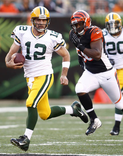 Green Bay Packers quarterback Aaron Rodgers (12) runs past Cincinnati Bengals linebacker Roddrick Muckelroy in the first half of an NFL preseason football game, Thursday, Aug. 23, 2012, in Cincinnati. (AP Photo/John Grieshop)